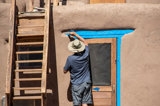 Back of Native American man in shorts and tee-shirt and sun hat painting bright blue-turquoise around the door of a mud adobe pueblo with wooden stairs to upper story