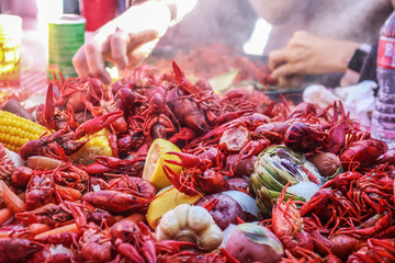 Pile of crawfish and carrots and vegetables on red checked tablecloth - food just out of the pot and steaming - selective focus
