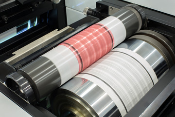 Flexography printing process on in-line press machine. Photopolymer plate stuck on printing cylinder, substrate is sandwiched between the plate and the impression cylinder to transfer the ink.