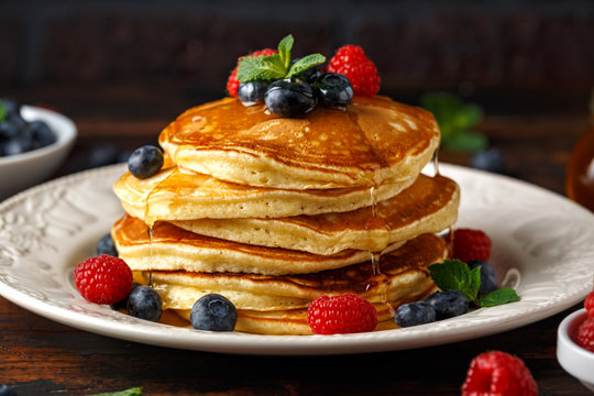 Homemade american pancakes with fresh blueberry, raspberries and honey. Healthy morning breakfast. rustic style