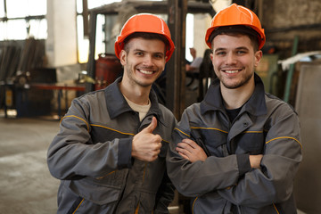 Portrait of two happy workers of metal stock in orange helmets and gray uniform standing together, posing and looking at camera. Man showing sight thumb up and his colleague standing with arms folded.