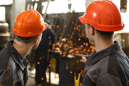 Back of two colleagues of metal stock in gray protective suits and orange helmets standing together, looking at process of welding and discussing it. Welder and sparks on background.
