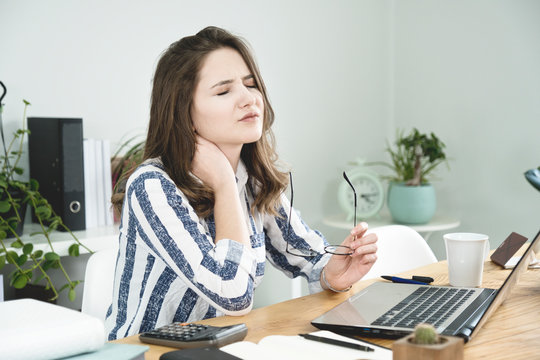 Young business woman having a neck pain.