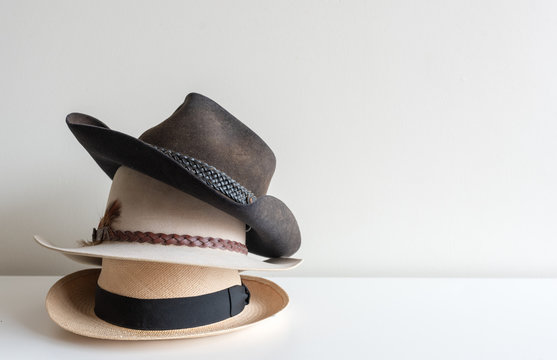 Three men's hats stacked on white shelf against neutral wall background with copy space