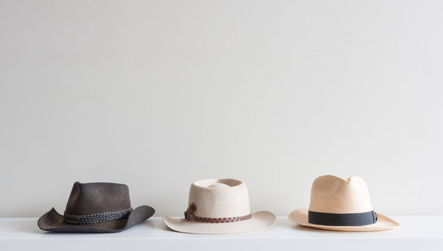 Three men's hats arranged on white shelf against neutral wall background