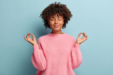 People, peace and meditation concept. Calm black young woman practices yoga indoor, shows okay sign with both hands, demonstrates approval, wears pink clothing, isolated over blue background Wall mural