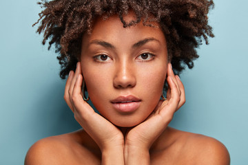 Close up shot of black young woman with Afro hairstyle, touches cheeks with both hands, has bare shoulders, tender look isolated over blue background, looks directly at camera. Horizontal shot