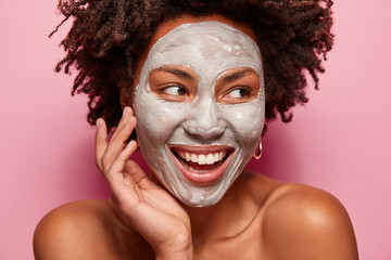 Printed kitchen splashbacks Spa Photo of glad black woman has clay mask, enjoys facial treatments, keeps gaze aside, touches face, has spa therapy, broad smile with white teeth, isolated over pink background. Perfect skin concept