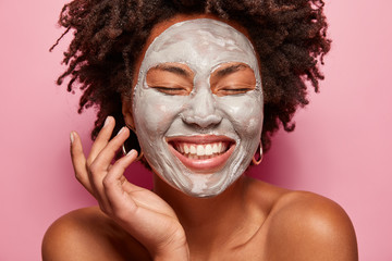 Professional skin care concept. Positive young woman with broad smile, has mask on face applied by beautician, touches soft skin, isolated over pink background. Cosmetics treatments concept.