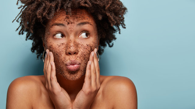 Curious black lady focused aside has coffe scrub on face applies mask on face, focused aside, has bare shoulders, isolated over blue background with blank space for promotion. Body care. Cosmetology