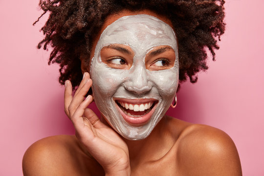 Photo of glad black woman has clay mask, enjoys facial treatments, keeps gaze aside, touches face, has spa therapy, broad smile with white teeth, isolated over pink background. Perfect skin concept