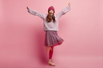 Inspired beautiful overemotive woman clenches fists, spreads hands, stands on one leg, spends time dancing and has fun, wears knitted hat, loose sweater, fashionable skirt, pink pantyhose, celebrates