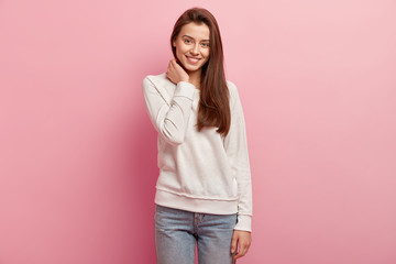 Isolated shot of positive young woman keeps hand on neck, looks directly at camera with pleasant toothy smile, shows white teeth, dressed in casual jumper and jeans, isolated over pink background