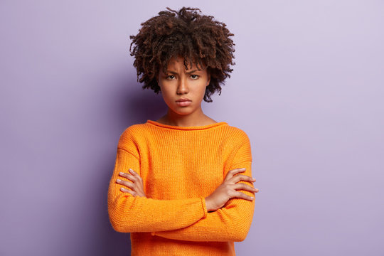 Angry sad young black female model crosses hands over chest, looks with grumpy expression, wears orange jumper, has Afro haircut, isolated over purple background. Negative human emotions concept
