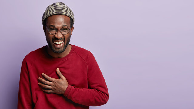 Stop telling such funny anecdotes. Dark skinned man keeps hand on chest, laughs out loudly, has fun with friends, smiles broadly, wears hat, spectacles and red jumper, feels amused and carefree