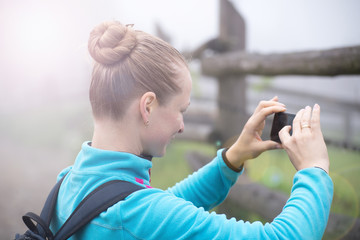 Young girl taking picture of wild place by smartphone