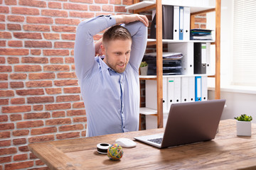 Businessman Stretching His Arms At Work Place