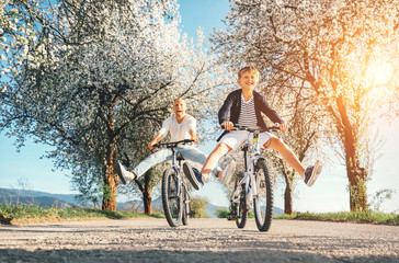 Father and son have a fun when riding bicycles on country road with blossom trees