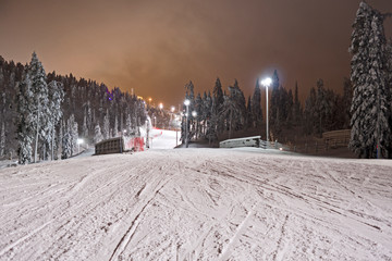 Kuusamo / Finland: View from the illuminated Talvijarvi slope to the upper lifts and slopes in the Ruka ski area on a mystic evening in February