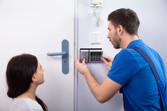 Handyman Installing Security System Near Door Wall