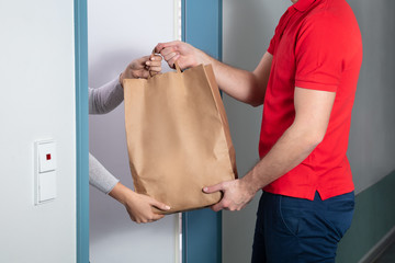 Man Giving Paper Bag To Woman