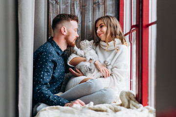 Happy smiling and attractive couple candid having fun with their cat on interior studio decoration