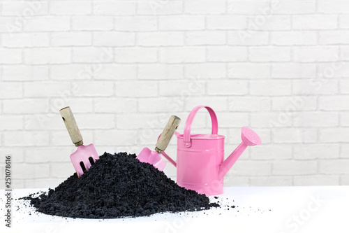 Pink Garden Tools And Watering Can With Compost Earth Pile The Trowel Fork Are