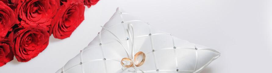 Panoramic image wedding rings red roses