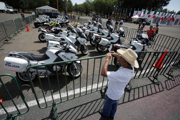 A man takes a picture of motorcycles, part of the fleet of government vehicles during an auction organized by the federal government at Santa Lucia military base on the outskirts of Mexico City