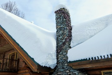 A closeup view of a stone chimney attached to a remote log cabin covered in freshly fallen snow.