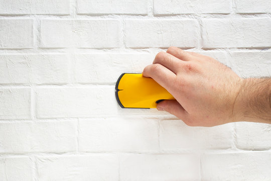 Man works with a wireless building tool to detect wooden battens on the background wall brick.