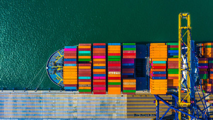 Container cargo freight ship with working crane bridge discharge at container terminal, Aerial top view container ship at deep sea port.