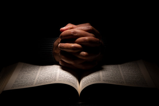 African American Man Praying with Hands on Top of the Bible.