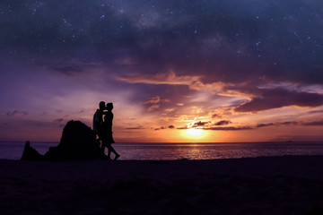 Silhouette couple kissing on the beach  with million stars galaxy and purple sky