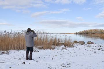 Birder by a bay in winter season