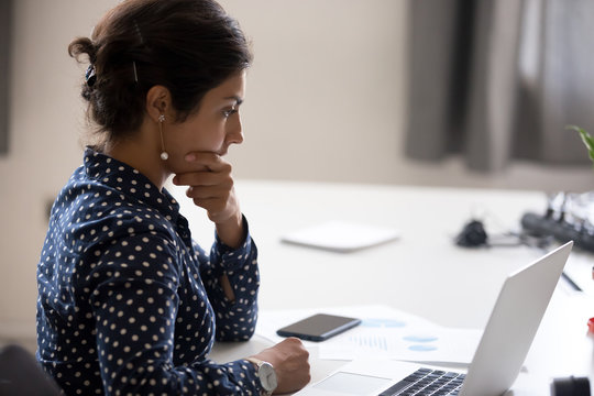 Concentrated serious office worker millennial woman analysing results