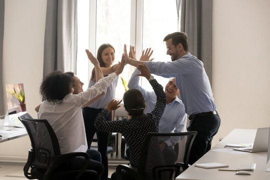 Diverse group of people giving high five in office