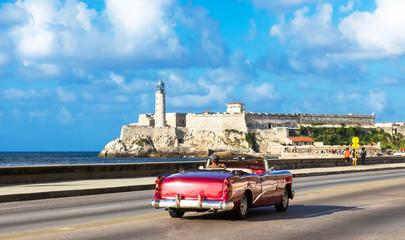 Amerikanischer purpur farbener Cabriolet Oldtimer auf dem berühmten Malecon und im Hintergrund die Festung Castillo de los Tres Reyes del Morro in Havanna Kuba - Serie Kuba Reportage Wall mural