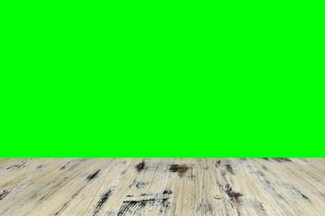 old painted washed oak wood table on the blurry chroma key green screen wall background, wooden table.