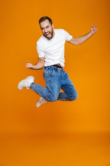 Full length photo of unshaved guy in t-shirt and jeans jumping and having fun, isolated over yellow background