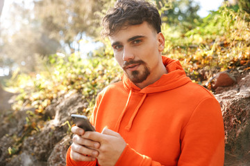 Handsome young sports fitness man runner outdoors in park using mobile phone.