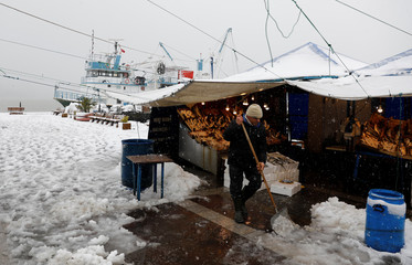A street vendor shovels snow in front of his stand during a foggy and snowy Sunday morning in Istanbul
