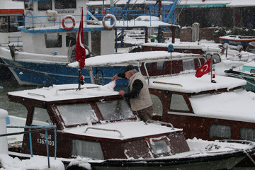 A fisherman shovels snow from his boat during a foggy and snowy Sunday morning in Istanbul,
