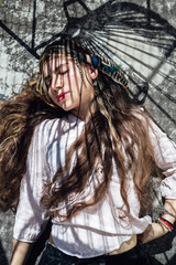 From above beautiful ethnic hippie female keeping eyes closed while lying on concrete floor on sunny day