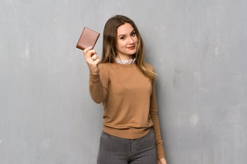 Teenager girl over textured wall holding a wallet