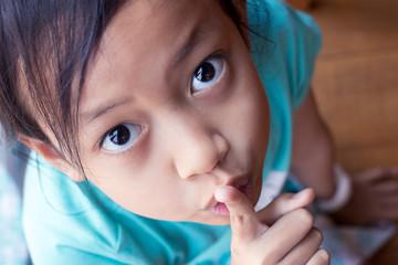 Closeup portrait secretive asian child girl placing finger keep quiet gesture Wall mural