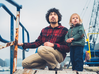 Father and toddler son admiring industrial shipyard
