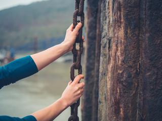 Young woman yanking a big rusty chain