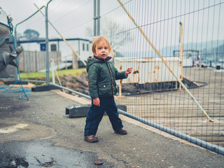 Little toddler standing by fence in boatyard