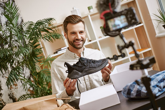 Sport shoes. Cheerful male blogger holding black sneakers while recording new video for his blog.